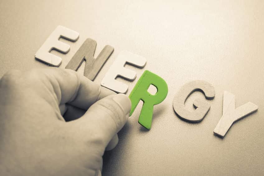 Hand arrange wood letters as Energy word